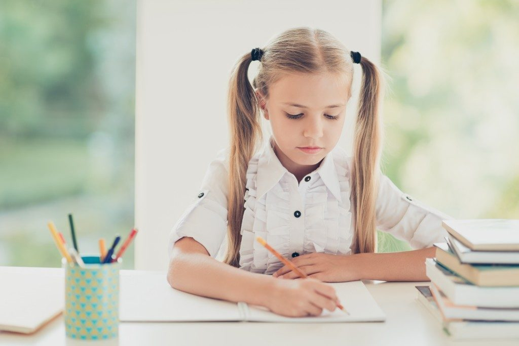Little girl writing on notebook