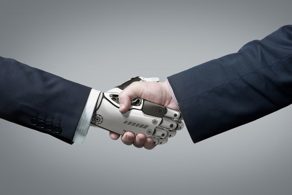 man shaking a robotic hand