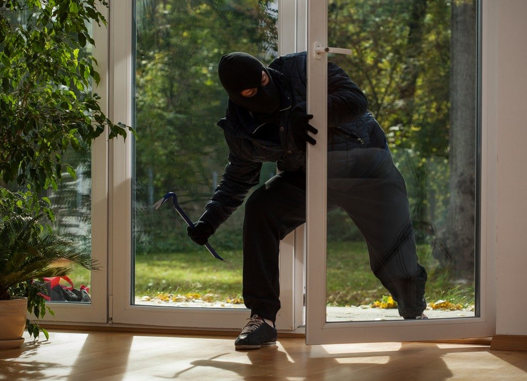 Burglar entering to house trough glass doors