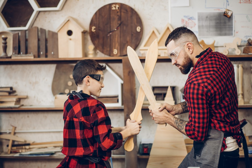 father and son playing with wooden swords