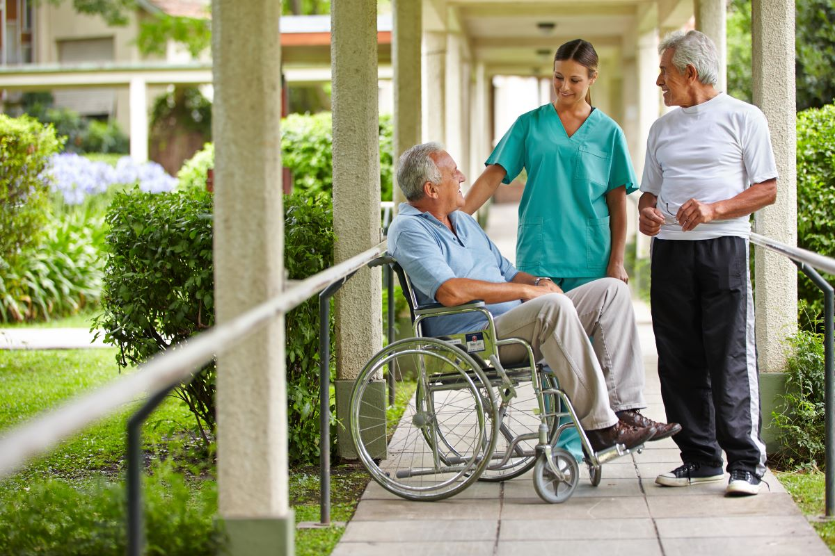 a senior citizen in a wheel chair talking to a nurse and another senior