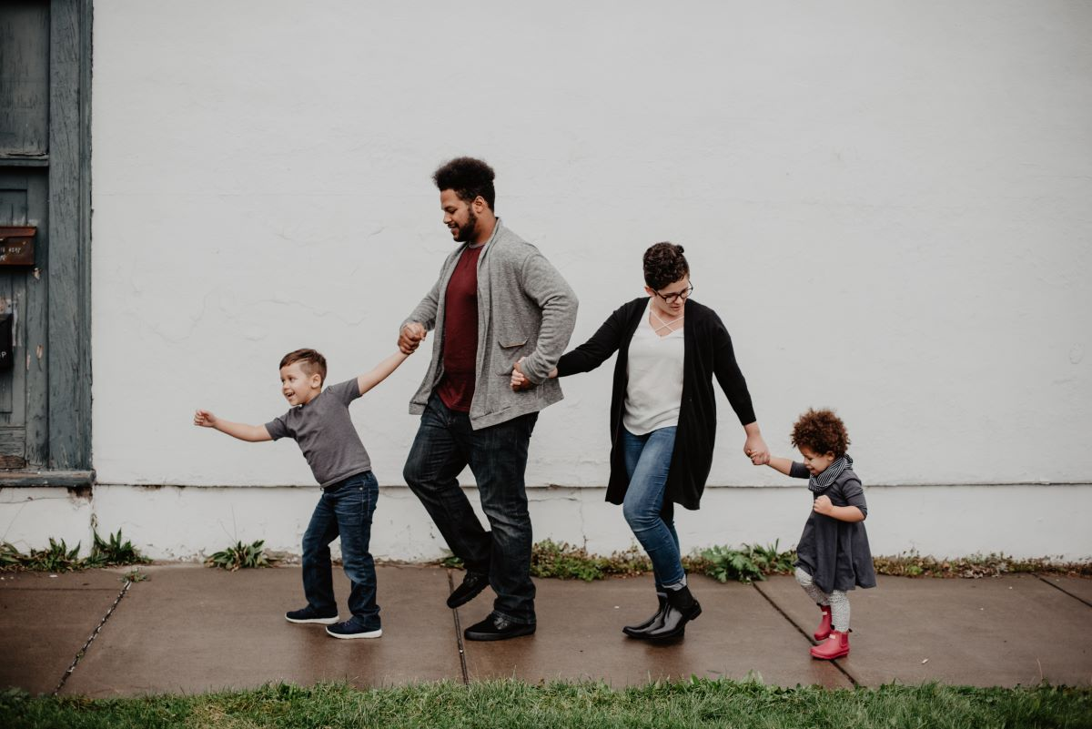 family of four walking holding hands