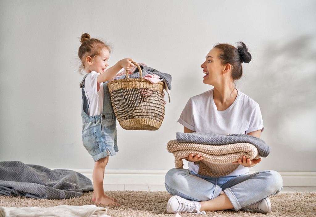 child helping her mother with the laundry