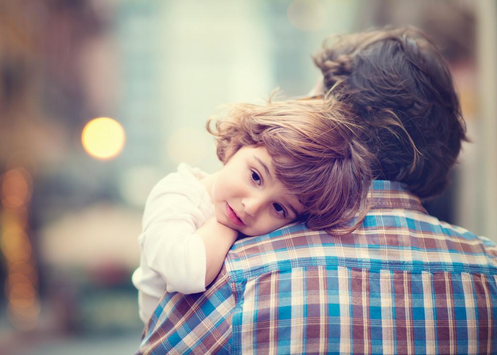 child resting on father's shoulder