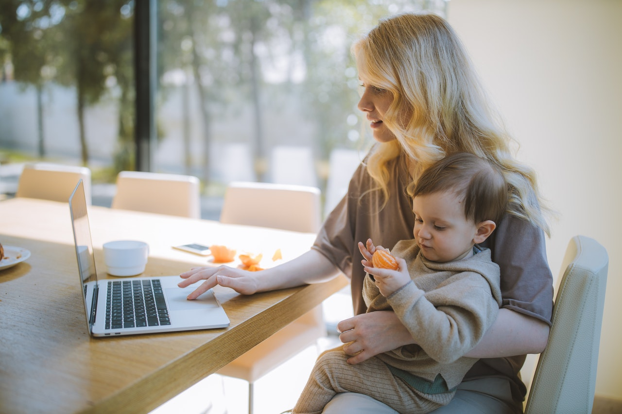 woman working while holding her baby