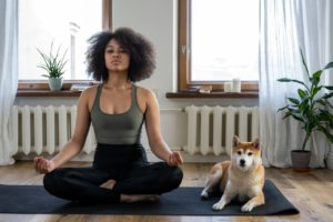 woman meditating with her dog
