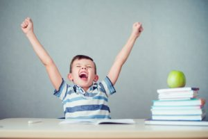 young boy cheering books