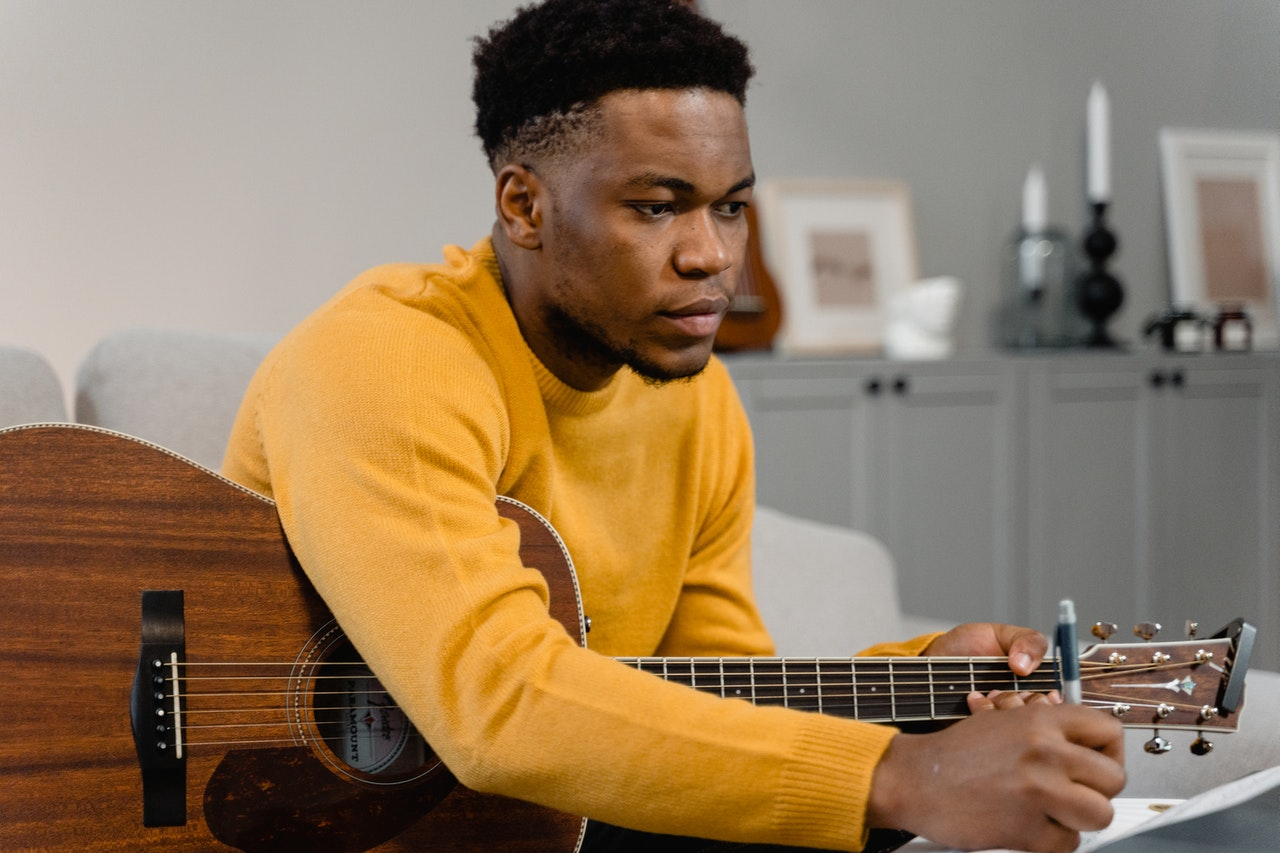 man learning to play guitar
